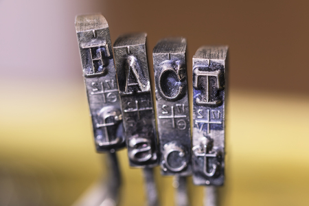 Macrophotography of typewriter hammers with FACT word.