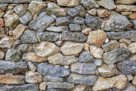 Detail of an old wall made of natural stone blocks