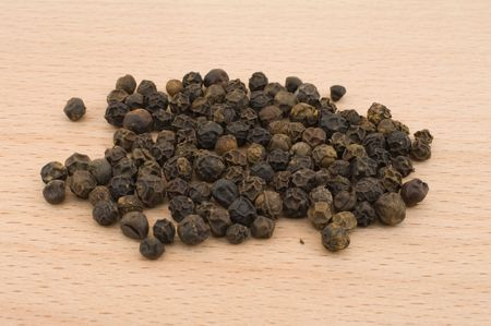 Heap of black pepper on a kitchen board photo