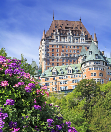 Chateau Frontenac with violet flowers on the foreground Editorial