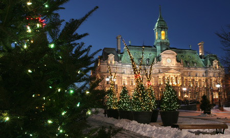 decorating christmas tree: City Hall at Montreal and Christmas trees at dusk Stock Photo