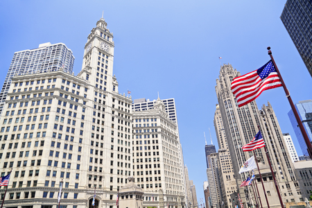 michigan avenue: Wrigley Building and Tribune Tower on Michigan Avenue with American flag on the foreground in Chicago, USA