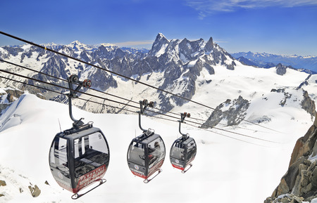Tourists enjoying the majestic landscape in gondolas from Point Helbronner to Aiguille du Midi. Redactioneel