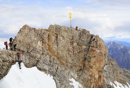 zugspitze mountain: Climbers at the cross on the summit of Zugspitze Mountain, the highest in Germany. Stock Photo