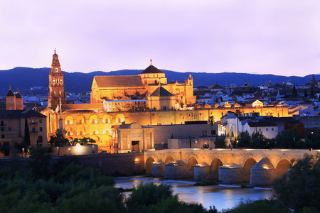 Roman Bridge and Guadalquivir River illuminated at dusk, Great Mosque in Cordoba, Spain Imagens