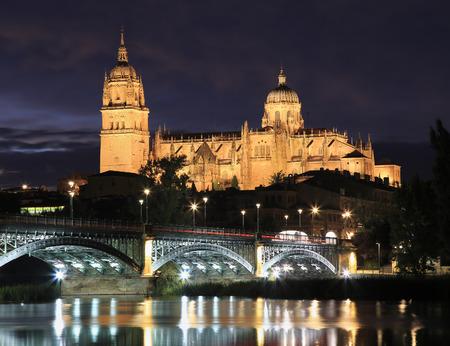 Salamanca skyline at night and Enrique Esteban Bridge over Tormes River in Spain Stock Photo