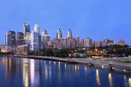 Philadelphia skyline illuminated and reflected into Schuylkill River at dusk, USA Stock Photo