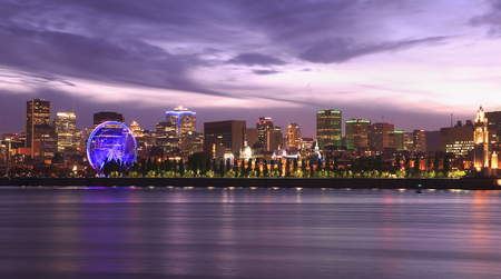 Montreal skyline and Lawrence River illuminated at dusk, Quebec, Canada
