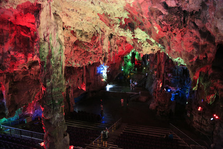 Tourists enjoying the colorful illuminated St. Michaels Cave. Is the name given to a network of limestone  at a height of over 300 meters above sea level. Фото со стока