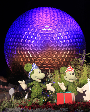 Disneys EPCOT Center sphere illuminated at night during Holidays Season with Mickey Mouse, Minnie and Pluto characters grass sculptures on the foreground