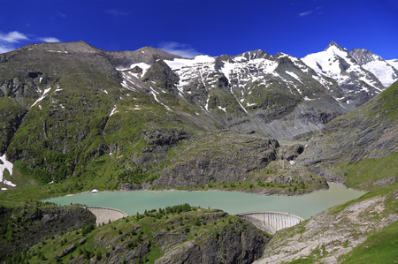Grossglockner High Alpine Road and summit with green lake and dam on the foreground, Austria
