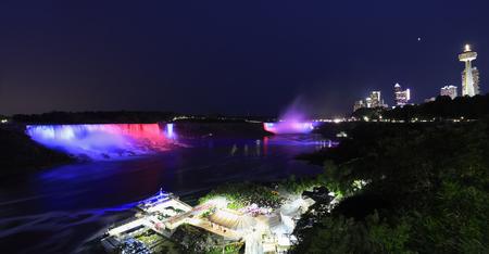 Horseshoe and American Falls, river and Niagara skyline illuminated at night, panoramic view, Canada