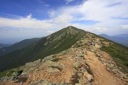 Hikers trekking along Franconia mountain ridge traverse, with a beautiful landscape background and blue sky. Mount Lafayette, Mount Lincoln, New Hampshire, USA