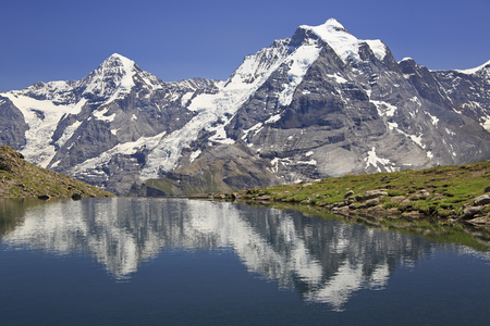Summer in the Swiss Alps, Murren area, overlooking the Monch and Jungfrau mountains reflected in Grauseewli Lake, Canton of Bern, Switzerland, Europe Stock Photo
