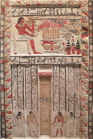 Ancient Egyptian engraved stone (pained bas-reliefs, signs and symbols telling stories) Editorial