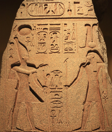 Engraved figures and  hieroglyphs of an ancient Egyptian stone wall