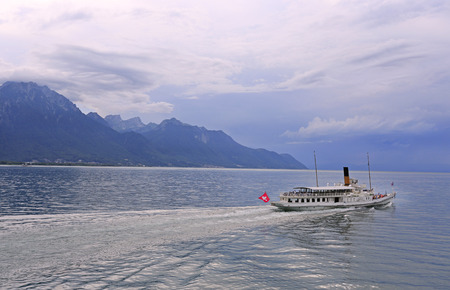 Cruise steamer on Lake Geneva against the background of beautiful mountains and reflection in the water before the storm, Switzerland