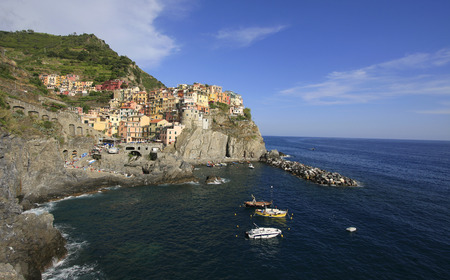 Colorful village of Manarola with fisher boats on the foreground, Cinque Terre, Italy