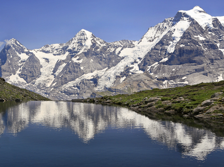Eiger, Monch and Jungfrau mountains reflected in Grauseewli Lake, Switzerland Alps Фото со стока