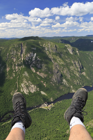 Hiker legs and boots at Acropolis of Draveurs above the canyon, Upper Gorges-de-la-Riviere-Malbaie National Park, Quebec in Canada