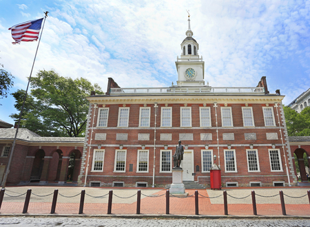 Independence Hall in Philadelphia including the American flag waving, Pennsylvania, USA.