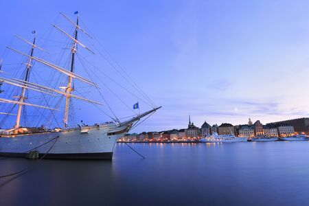 Scenic view of Stockholm's Old Town (Gamla Stan) at dusk with illuminated old ship on the foreground, Sweden Standard-Bild