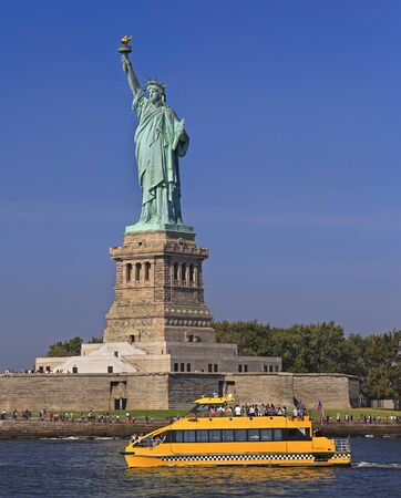 The statue of Liberty with yellow water taxi on the foreground, New York City, USA