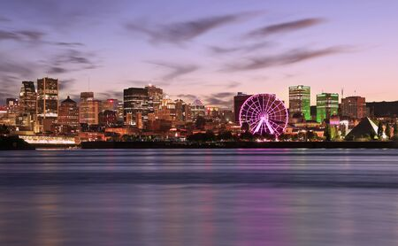 Montreal skyline illuminated at dusk reflected in Saint Lawrence River, Quebec, Canada Фото со стока