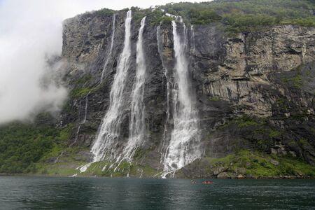 Kayak explorers at Seven Sisters waterfalls, Geiranger Fjord in Norway