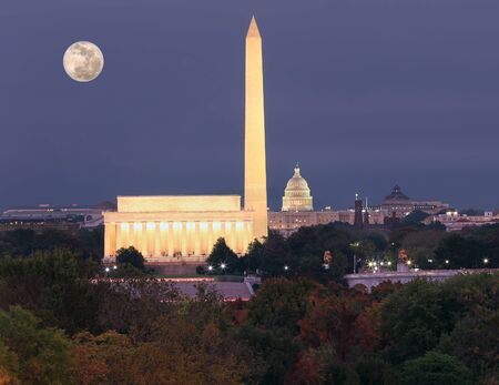 Washington DC skyline at dusk with autumn colorful trees on the foreground, USA