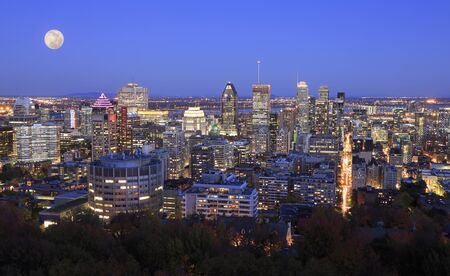 Colorful Montreal skyline at night including a beautiful full moon on the sky, Canada
