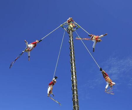 The Voladores, or flyers performance. They climb up a very high pole their waist to ropes wound around the pole and then jump off, flying gracefully around it. Editorial