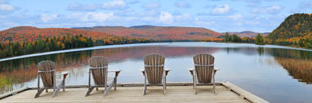 Wooden armchairs on Lake Monroe shore and autumn colors in Mont Tremblant National Park, Quebec 免版税图像