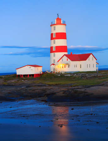 Pointe-des-Monts Lighthouse at dusk with reflections in the sea, Cote-Nord, Quebec 免版税图像