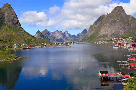 Sharp mountains, red huts and fishing boats reflected into the fjord in Reine, Lofoten Islands, Norway 免版税图像