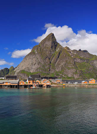 Sakrisøy Island with colorful yellow fishing houses in a sunny day, Lofoten, Norway