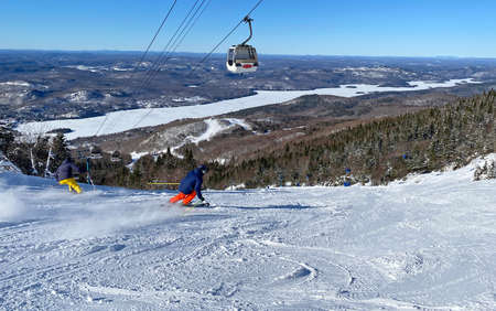 Skiers on Mont Tremblant slopes with aerial gondolas on the background, Quebec, Canada