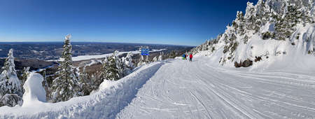Panoramic aerial view of Mont and Lake Tremblant in winter with skiers on slope downhill, Quebec, Canada