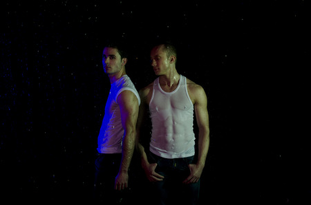 Two attractive young guy. Night. Wet body. Foto de archivo