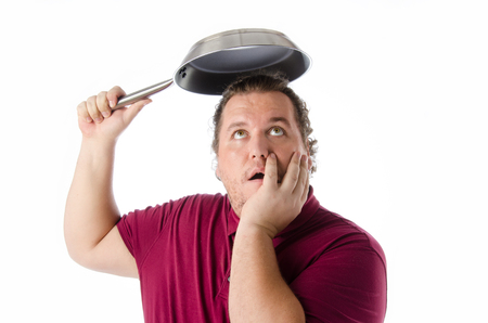 Funny man with a frying pan. Protection. Standard-Bild