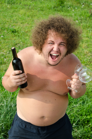 Funny fat guy with a bottle of wine 스톡 콘텐츠