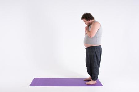 Divertido hombre gordo y yoga. Deporte, dieta y un estilo de vida saludable. Foto de archivo