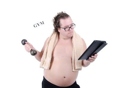 Healthy lifestyle. Fat man with a dumbbell and a tablet.