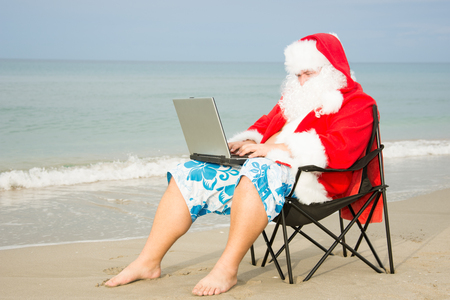 Funny Santa on the beach working on laptop