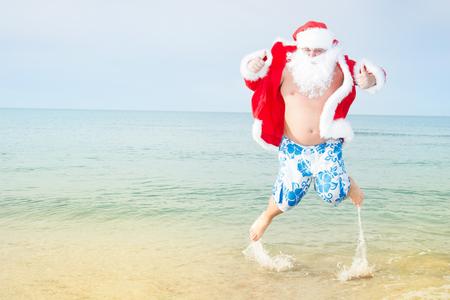 Funny Santa in shorts on the beach.