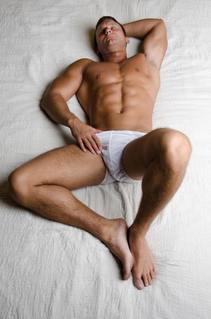 Man resting on the bed. Handsome man in underwear resting on the bed in the bungalow. Weekends and holidays.