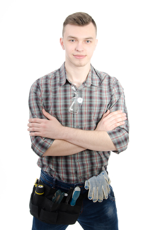 Young handsome handyman. White background. A handsome man in studio. Tools and businesslike. Serious and with a smile.