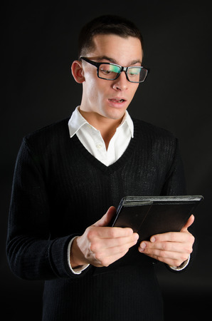 Young happy businessman holding a tablet. Joy and happiness. Business and success.