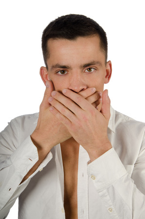 Young handsome guy covering his mouth with his hands. Handsome man closes his mouth with his hands. Speak no evil