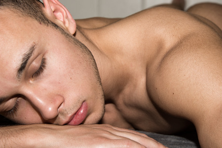Young sexy man sleeping on the bed. Handsome and attractive